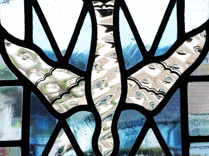 Stained glass window of a dove descending