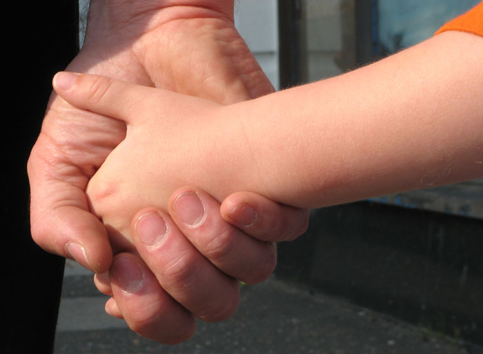 Photo of a Father holding his son's hand.