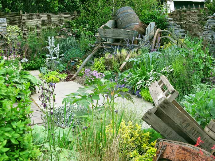 Photo of a garden with a muted mainly green planting with wooden crates and an old cart
