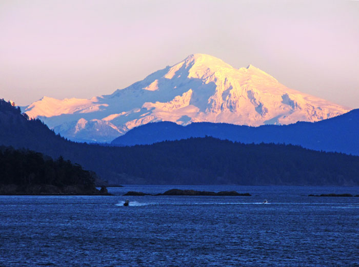 Photo of Mt Baker, Washington State at sunset, taken from Vancouver Island, with a speedboat on the foreground water coming toward the camera.