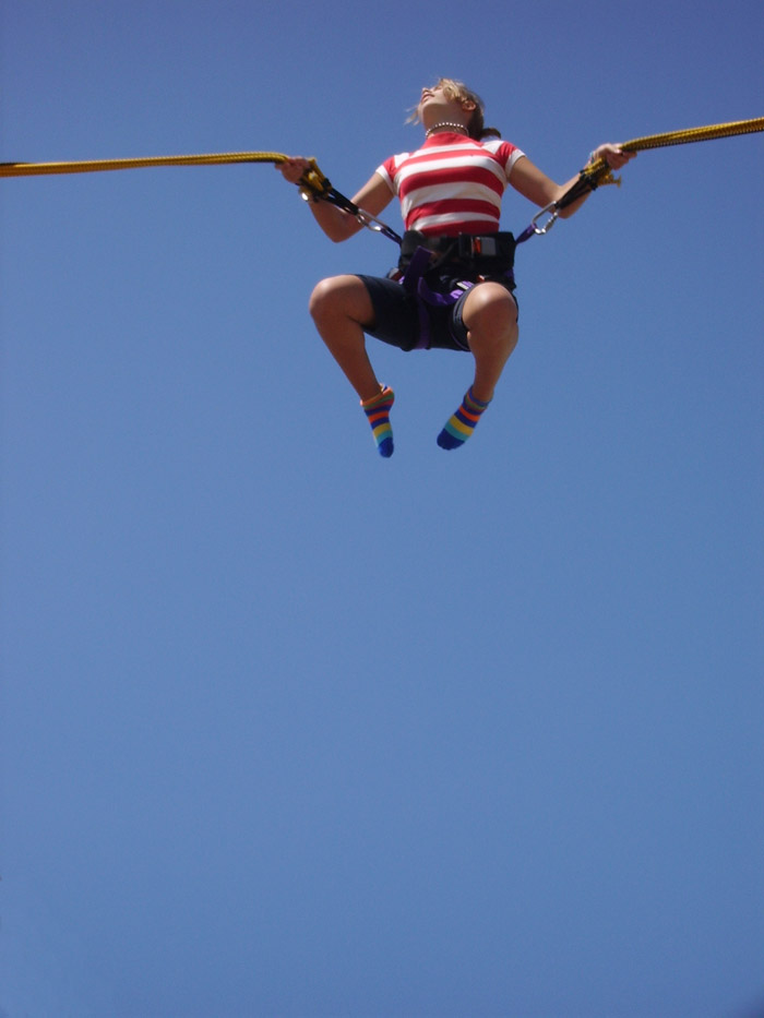 A young woman bounces high up into the air restrained by a harness