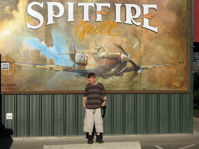 Tim 'wincing' while standing in front of a painting of a huge Spitfire which is flying towards him.
