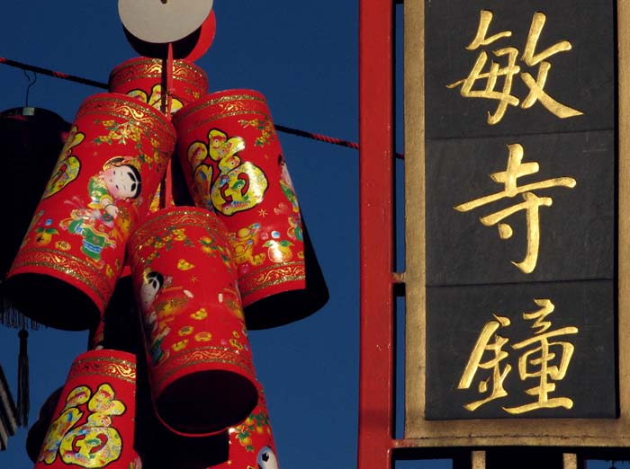 A Chinese sign with gold lettering glistens in the sun.