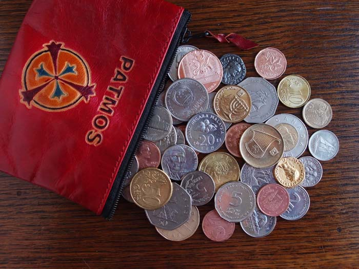 A red purse enscribed Patmos has spilled coins of the nations onto a table